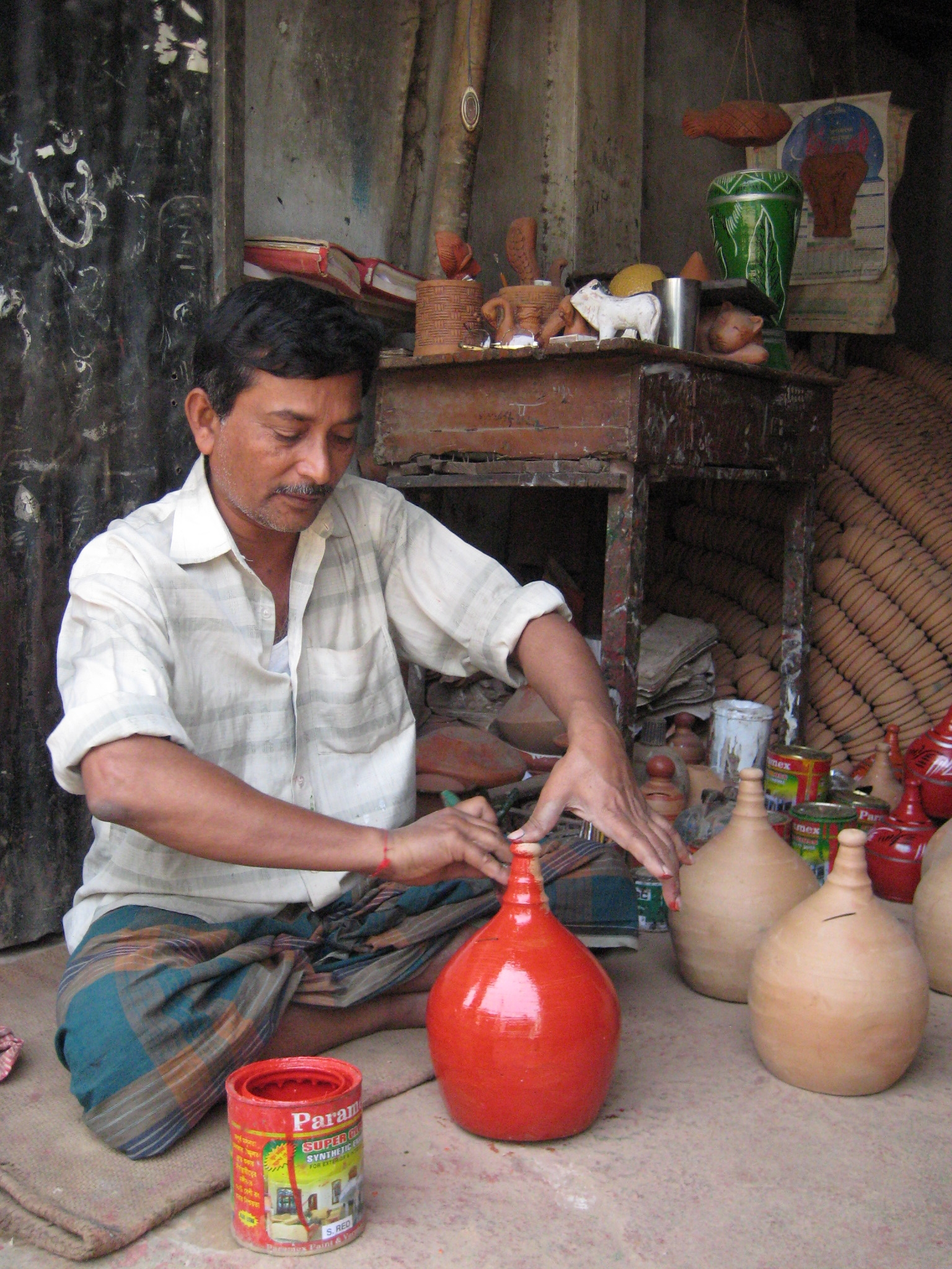 Man painting pottery in Banglades