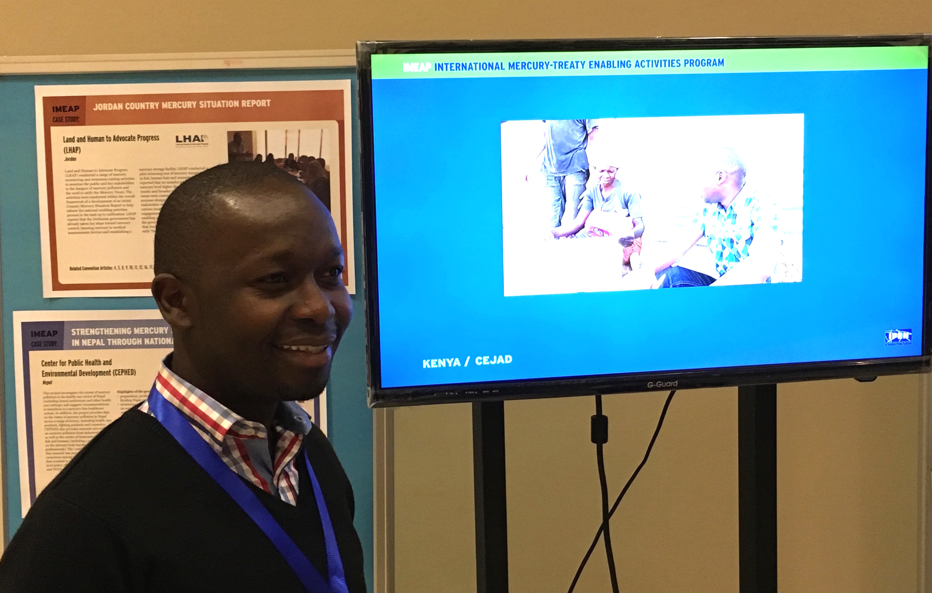 Griffins Ochieng (CEJAD) standing near the ASGM-related video that CEJAD produced for their IMEAP project with IPEN