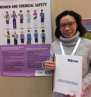 "Hang Pham, Vice Director of CGFED, at the IPEN exhibit holding the ""Stories of Women Workers in Vietnam's Electronics Industry"" report"